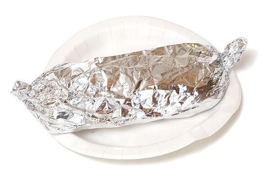 紙皿に乗ったチャバタホットサンドイッチ(アルミホイルに包まれている)