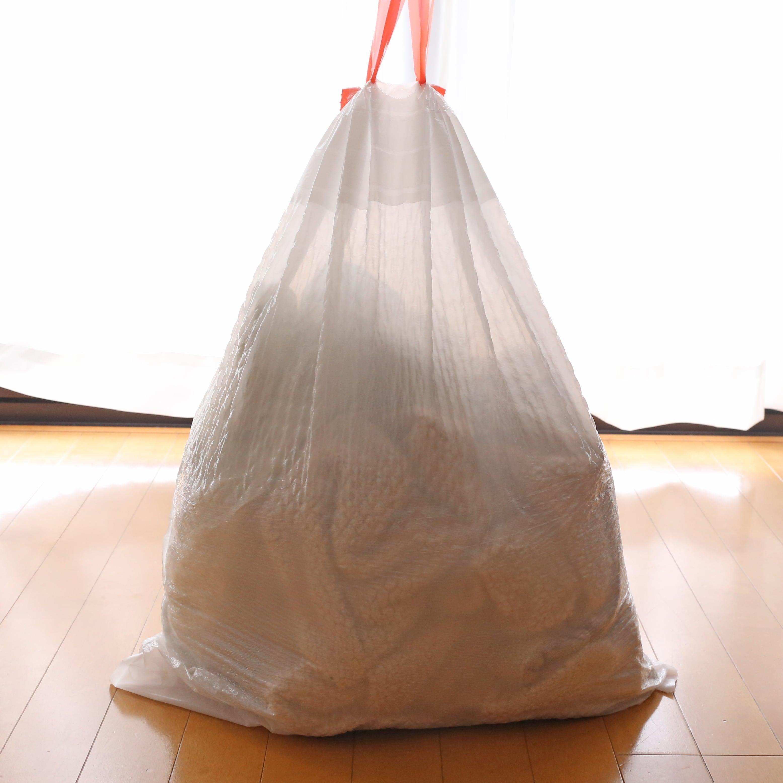 カークランドシグネチャー キッチンバッグ ひも付きゴミ袋 中にものを入れて口を絞った様子