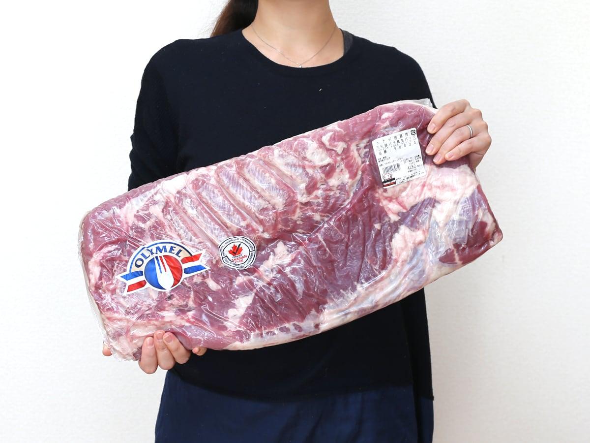 コストコの巨大な豚バラ塊の切り分け方 カナダポーク三元豚 豚バラ真空パック 手に持った写真